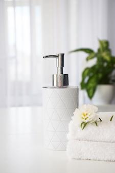 Toalhas brancas frescas dobradas na mesa branca, flor branca e recipiente de sabonete líquido com folhas verdes da planta da casa e janela de tule no fundo