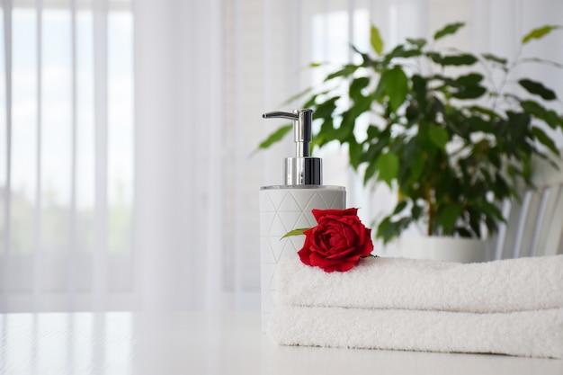 Toalhas brancas frescas dobradas sobre a mesa com rosa vermelha e dispensador de saboneteira com planta da casa e janela de tule no fundo. interior de casa aconchegante. conceito de spa ou salão de beleza. copie o espaço.