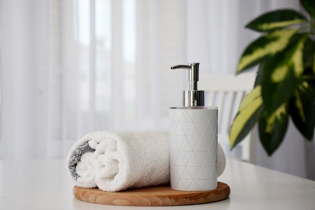 Toalhas brancas frescas enroladas na placa de madeira e no recipiente de líquido com folhas verdes da planta da casa e janela de tule no fundo. copie o espaço.