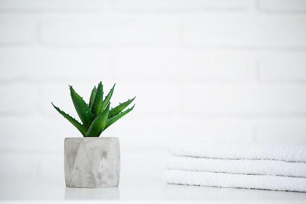 Toalhas brancas na mesa branca com espaço de cópia no banheiro