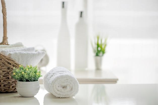 Toalhas brancas na tabela branca com espaço da cópia no fundo borrado do banheiro.