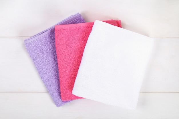 Toalhas brancas, roxas e cor-de-rosa em uma tabela de madeira branca.