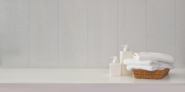 Toalhas com acessórios de spa na mesa branca com espaço de cópia