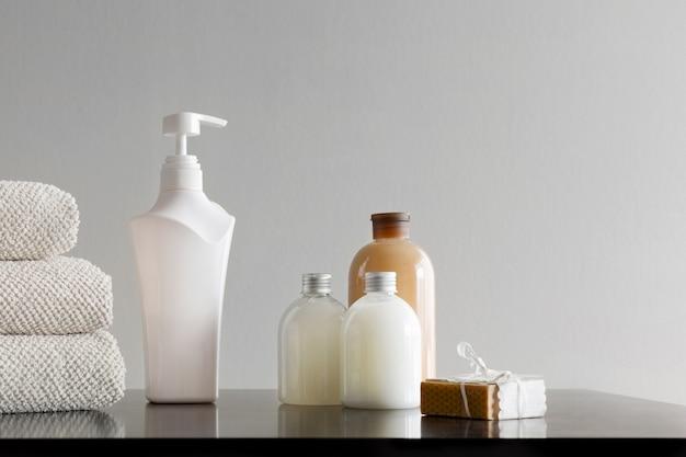 Toalhas com xampu, loção corporal, leite de banho e sabonete artesanal em fundo neutro.