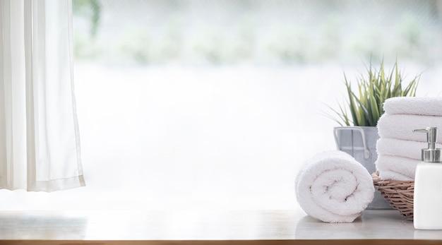 Toalhas de banho brancas limpas na mesa de madeira