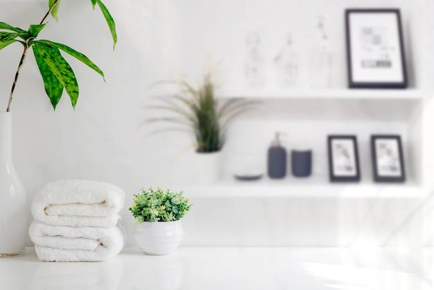 Toalhas de banho do modelo na tabela de madeira na sala branca com espaço da cópia.