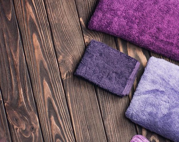 Toalhas de banho em fundo de madeira. toalha de banho azul e roxa