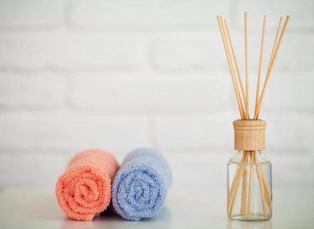 Toalhas de banho macias na mesa de madeira clara com varas de aroma