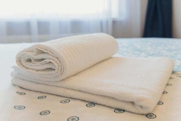 Toalhas de banho na cama do quarto do hotel.