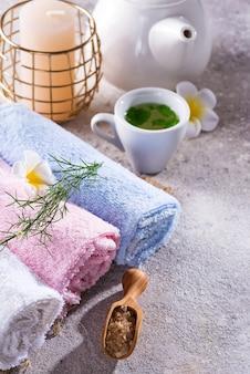 Toalhas de cor com flor, colher de sal, na esteira de bambu, tratamento de spa de banho e chá verde na mesa de pedra, copyspace