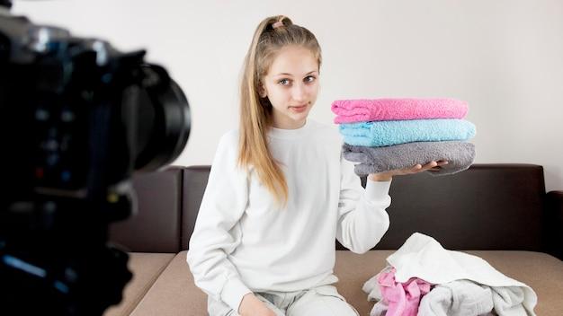 Toalhas de dobramento da menina do tiro médio