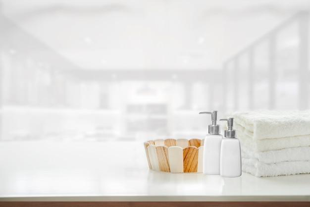 Toalhas de maquete, balde de madeira vazio e garrafa de sabonete na mesa branca