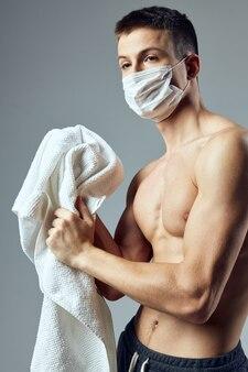 Toalhas de proteção contra vírus máscara médica homem desportivo no ginásio de mãos
