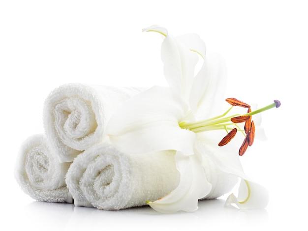 Toalhas de spa brancas com flor de lírio isoladas em branco. conceito de spa