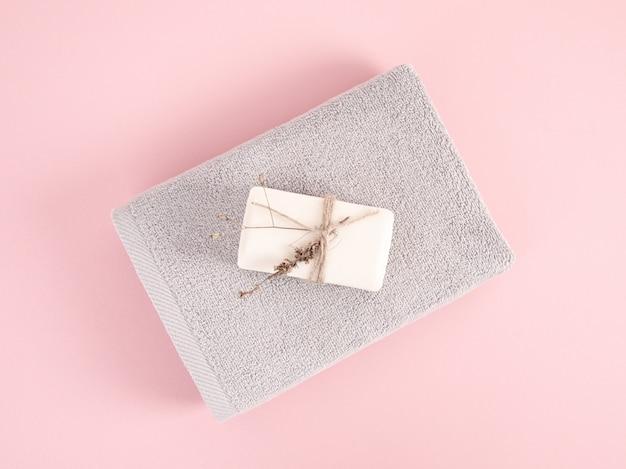 Toalhas de terry dobradas e empilhadas com sabão no fundo rosa