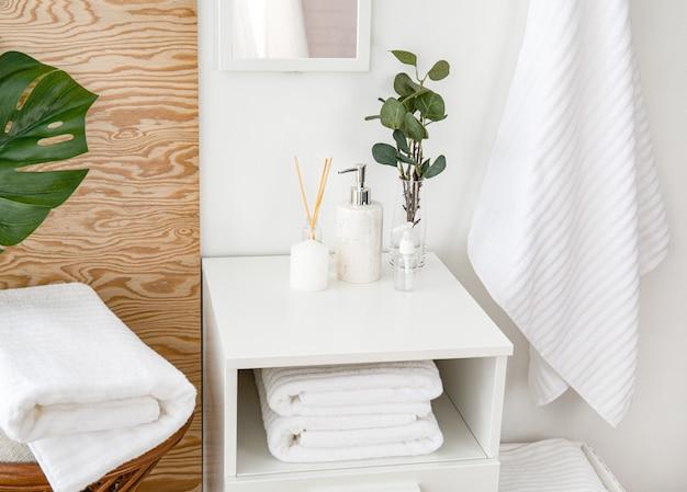 Toalhas de terry e composição dos acessórios do banheiro no interior. banheiro fresco e agradável, com elementos de madeira, flores, folhas tropicais de monstera e espelho.