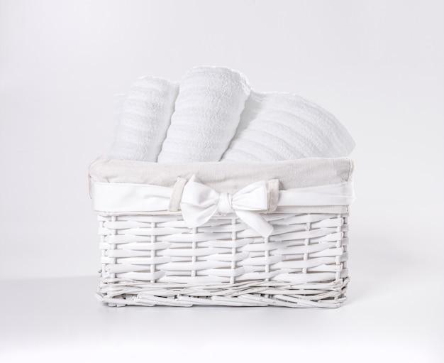 Toalhas de terry macias brancas roladas na cesta contra um contexto branco. toalhas listradas em uma cesta branca na frente de um contexto branco.