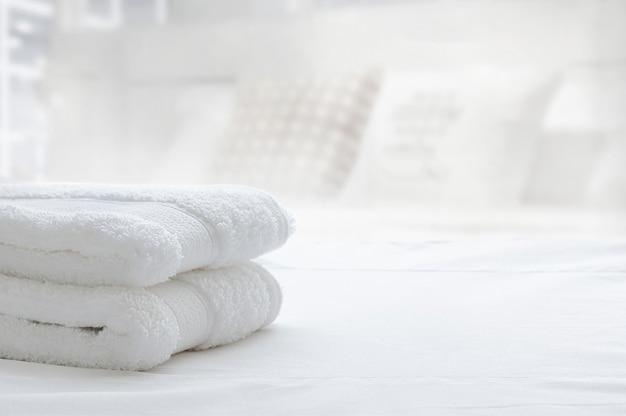 Toalhas dobradas brancas na cama branca, espaço da cópia.