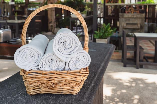Toalhas dobradas do rolo empilhadas na cesta de madeira