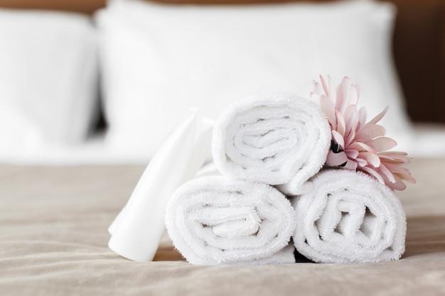 Toalhas e flor na cama no quarto de hotel