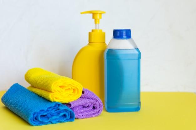 Toalhas e garrafas plásticas com produtos de limpeza