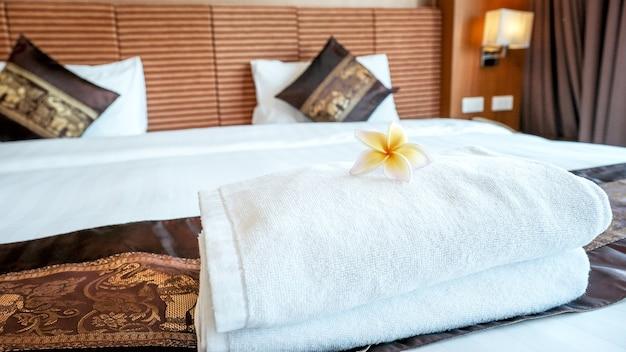 Toalhas e plumeria na cama no quarto de hotel de luxo pronta para viagens turísticas.