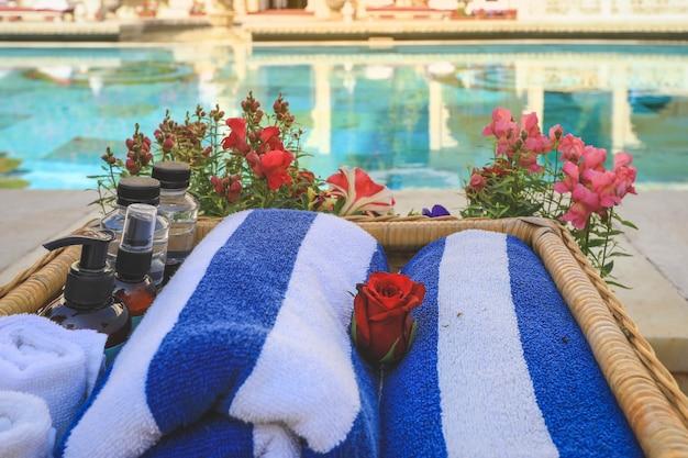 Toalhas enroladas e frascos para os cuidados com a pele estão na cesta perto de uma piscina. conceito de relaxamento de verão