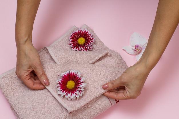 Toalhas felpudas macias e mãos femininas com crisântemos em fundo rosa. vista do topo.