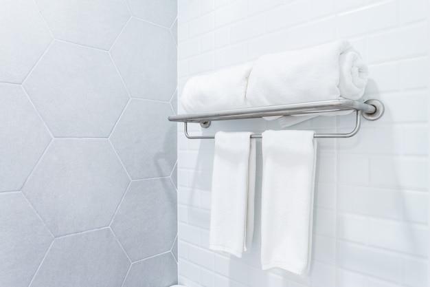 Toalhas limpas com o gancho no fundo do interior do banheiro da parede.