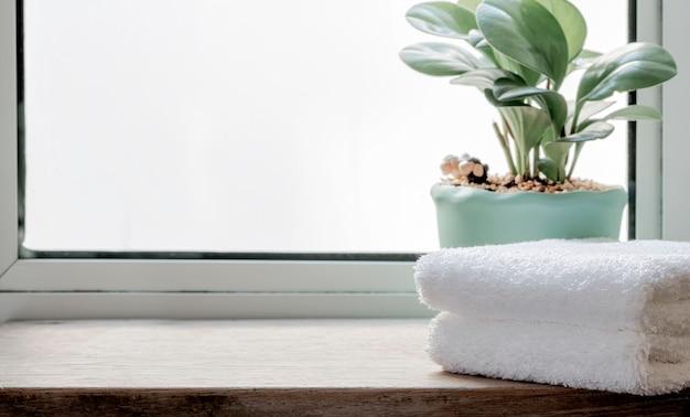 Toalhas limpas dobradas com planta de casa na mesa de madeira. copie o espaço.