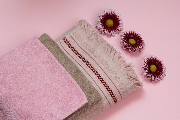 Toalhas macias de terry com botões de flores em fundo rosa. vista do topo.