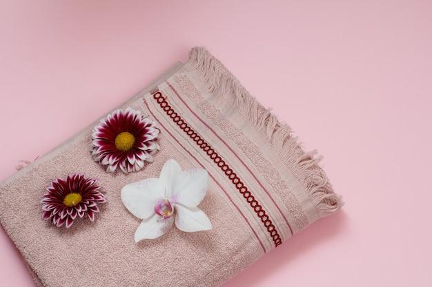 Toalhas macias de terry com orquídea branca e botões de flores em fundo rosa. vista do topo.