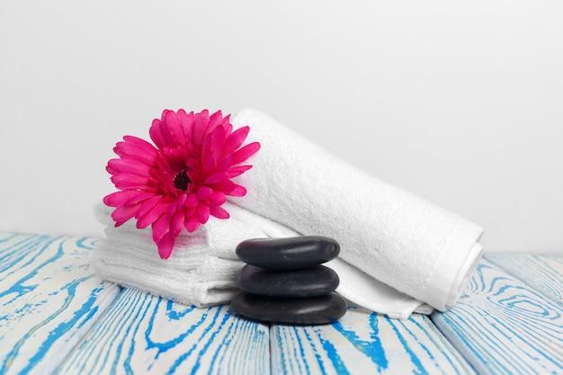 Toalhas macias limpas com flor na mesa de madeira