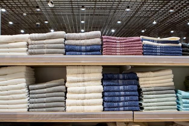 Toalhas multicoloridas dobradas nas prateleiras.