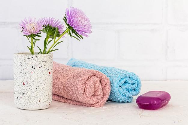 Toalhas, sabonete e flores de ásteres em um fundo branco. cosméticos femininos e acessórios de lavagem.