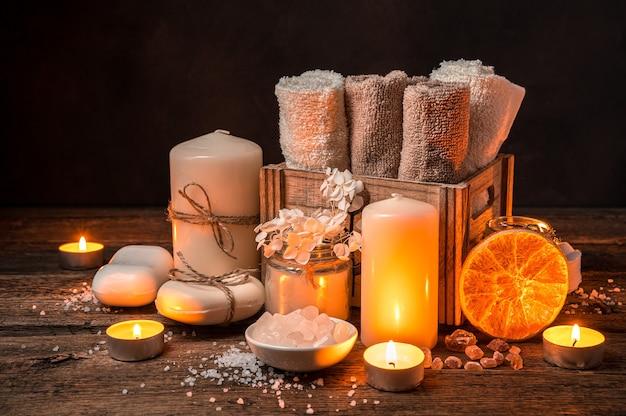 Toalhas, sabonete, sal, uma rodela de laranja seca e velas acesas. kit de spa.