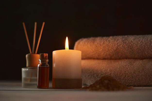 Toalhas, vela e óleo de massagem na mesa branca