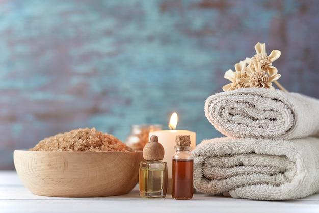 Toalhas, velas e óleo de massagem na mesa branca