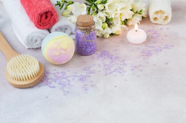 Toalhas, velas, sal, sabão, escova, pano de lavar roupa e buquê de freesia