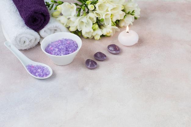Toalhas, velas, sal, um buquê de frésias e pedras - itens para um procedimento de spa
