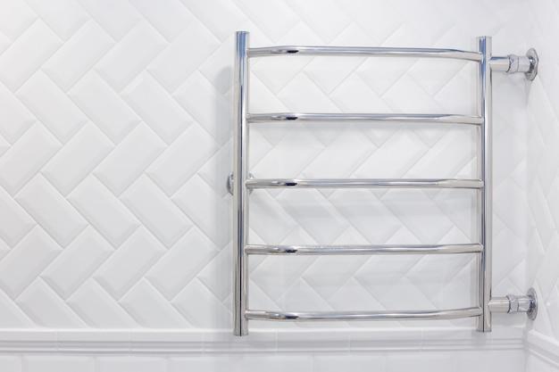 Toalheiro aquecido com conexão lateral em um banheiro de tijolos brancos.