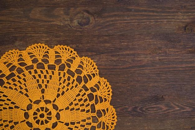 Toalhinha de crochê amarela sobre a mesa de madeira marrom