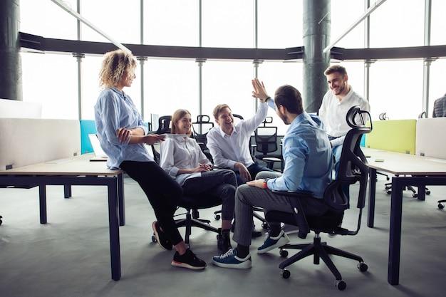 Toca aqui! alegres jovens empresários dando mais cinco enquanto seus colegas olhando para eles e sorrindo.