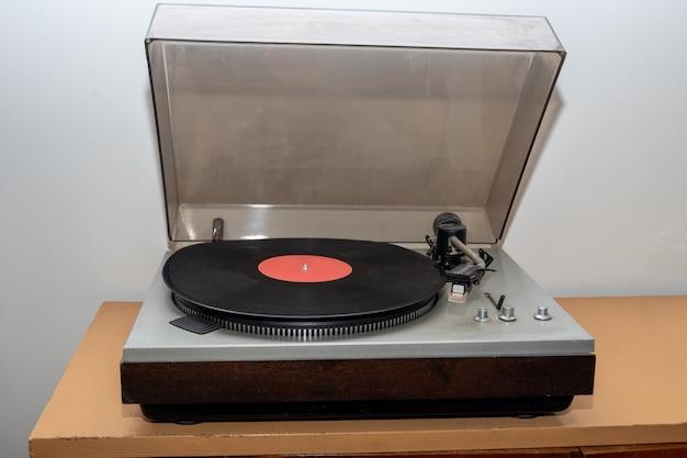 Toca-discos estéreo vintage retrô analógico em uma mesa de madeira. uma plataforma giratória de plástico antiquada tocando uma faixa de música, vista frontal. conceito de música retro