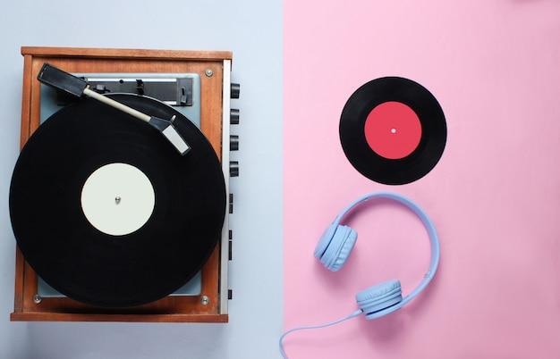 Toca-discos vinil retrô, fones de ouvido no fundo cinza rosa