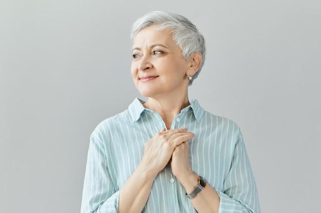 Tocada agradecida encantadora aposentada caucasiana de meia-idade olhando para longe com um sorriso amável de agradecimento, mostrando gratidão e apreço pelo amor, apoio, votos cordiais, apoio e carinho