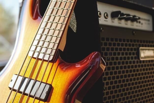 Tocando guitarra de perto, a guitarra elétrica marrom e o amplificador