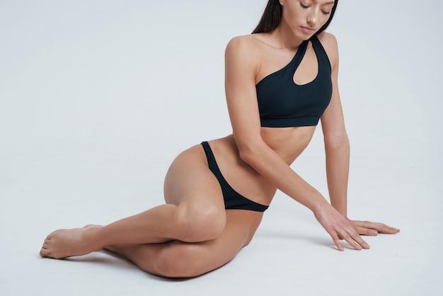 Tocando o chão. menina com corpo jovem tonificado magro perfeito.