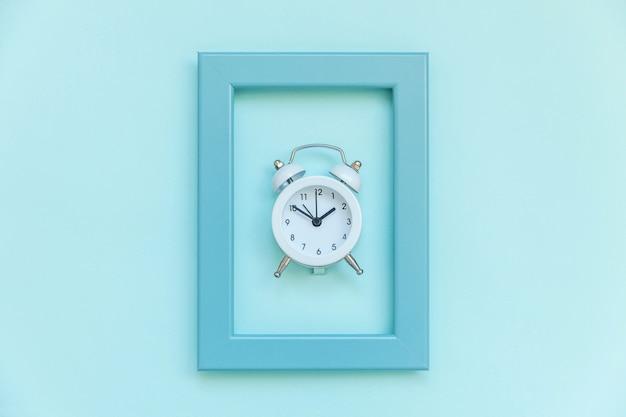 Tocando o sino gêmeo vintage despertador no quadro azul isolado