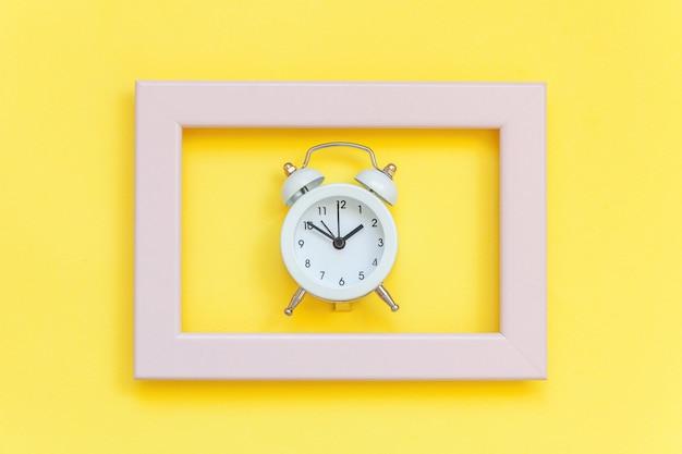 Tocar o sino duplo despertador vintage no quadro rosa isolado na moda colorida amarela